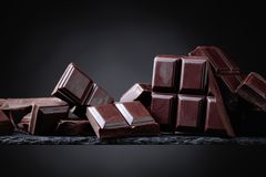 Broken chocolate pieces on a black background. Stock Image