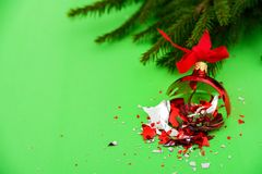 Broken Christmas ball on green background. Broken red Christmas ball on green background with tree branch stock images