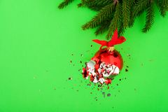 Broken Christmas ball on green background. Broken red Christmas ball on green background with tree branch royalty free stock photography