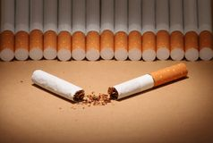 Broken cigarette. A broken cigarette illuminated and few cigarettes on the background stock images