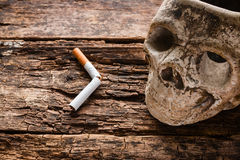 Broken cigarette and ashtray in the form of the skull. Smoking kills concept stock image