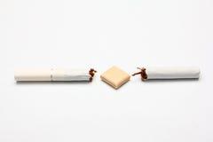 Broken cigarette and gum Stock Photos