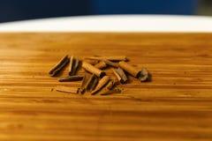 Broken cinnamon sticks. On a wooden board Stock Photo