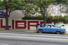 Broken classic american car parked in Havana, Cuba. An old and broken american car in front a cuban propaganda sign Stock Photos