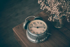 Broken classic clock on wood table with dry flower vase Royalty Free Stock Photography