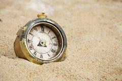 Broken clock. Old broken clock buried in sand Royalty Free Stock Images