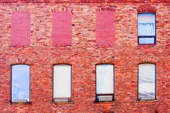 Broken Communication. A reddish brick wall with a matrix of eight windows, two by four, three of them covered with red bricks Stock Photo