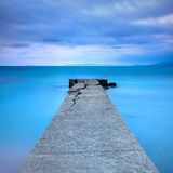 Broken concrete pier or jetty and rocks on a blue sea. Hills on background Royalty Free Stock Image