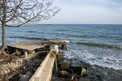 View of broken concrete pier in the sea, coastal destruction with single tree and blue sky stock photo