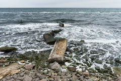 Broken concrete slabs on the rocky shore. Among the rocks and waves Stock Photography