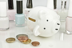 Broken on cosmetics - piggy bank, coins, nail polish Stock Images