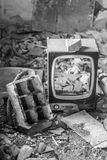 Broken CRT Television Set in abandoned room. With many pieces of broken objects and dirt, in black and white Stock Images