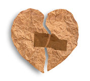 Broken crumpled paper heart coupled with tape Royalty Free Stock Photography