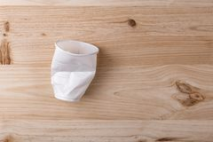 Broken crumpled white plastic Cup lies on a wooden table of natural color. The concept of abandonment of plastic for nature conservation royalty free stock photo