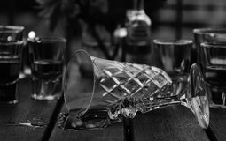 Broken crystal glass. Black and white image with a broken crystal glass and spilt liquid on table surrounded by smaller half-filled glasses. Party mood and bokeh royalty free stock photo