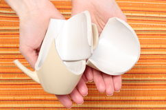 Broken cup lying on hand of woman Stock Photo