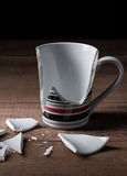 Broken cup. On wooden background Stock Images