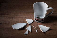 Broken cup. On wooden background Royalty Free Stock Photos
