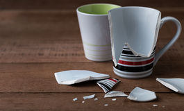 Broken cup. Broken cup on wooden background Royalty Free Stock Image