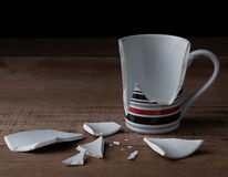 Broken cup on wooden background. Vintage style Royalty Free Stock Photos