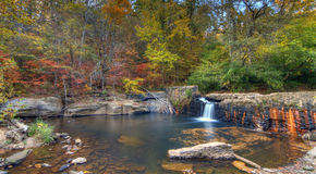 Broken Dam. Small waterfall in a broken dam surrounded by early fall foliage at Freeman Mill Park near Atlanta, Georgia Royalty Free Stock Photos