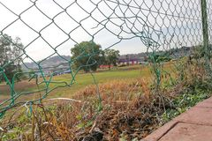 Broken damaged chain fence with hole. In neighborhood Stock Photo