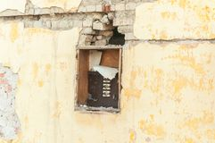 Broken and damaged electric fuse box on demolished house in the war conflict zone.  royalty free stock photos