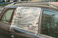 Broken and damaged shattered glass of the car side window protected with nylon and duct taped to protect interior from rain and wa. Ter stock photography