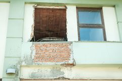 Broken and damaged window with hole in the facade of the house or building waiting to be replaced stock photos