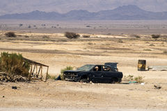Broken dark blue car without wheels. Stands in the Arava Valley against the background of the Edom Mountains Royalty Free Stock Image