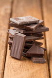 Broken dark chocolate bar on a wooden table Royalty Free Stock Photo