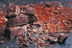 Broken dark chocolate, cocoa powder and coffee beans. On a wooden table stock photography