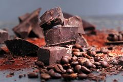 Broken dark chocolate, cocoa powder and coffee beans. On a wooden table stock image