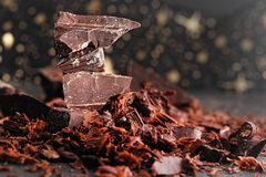 Broken dark chocolate, cocoa powder and coffee beans. On a wooden table royalty free stock image