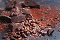Broken dark chocolate, cocoa powder and coffee beans. On a wooden table royalty free stock photo