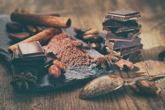 Broken dark chocolate, cocoa powder and coffee beans. On a wooden table royalty free stock photos