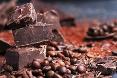 Broken dark chocolate, cocoa powder and coffee beans. On a wooden table stock images