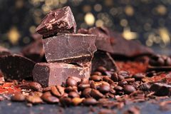 Broken dark chocolate, cocoa powder and coffee beans. On a wooden table stock photos