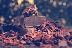 Broken dark chocolate, cocoa powder and coffee beans. On a wooden table royalty free stock photography