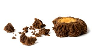 Broken dark cookies and crumbs on a white, isolated. stock images