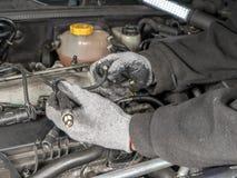 Broken Diesel glow plug wire. Auto mechanic replacing broken Diesel glow plug wire in car diesel engine compartment Royalty Free Stock Photo