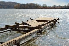 Broken dock. Broken wooden dock in the waves of the river Stock Photography