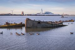 Broken docking bricks at river Thames during sunset. With ducks and industrial buildings in the background Royalty Free Stock Images