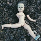 Broken doll on the ground - creepy halloween stock photography