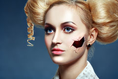 Broken doll. Halloween broken doll beautiful girl with perfect make up and hairstyle over dark blue background stock photo