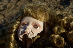 Broken doll head on the ground. Broken head of porcelain doll lying on the ground Stock Images