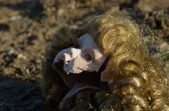 Broken doll head on the ground. Broken head of porcelain doll lying on the ground Royalty Free Stock Photo