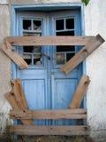 Broken door. Broken plank in front of blue doors. Security concept Royalty Free Stock Images