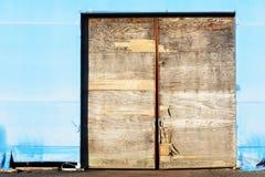Broken door. A broken and weathered wooden door on a temporary plastic warehouse Stock Photo