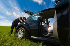 Broken Down. Car in field with doors open and back door up.  Man checking car in back.  Woman sitting inside car waiting Stock Photos